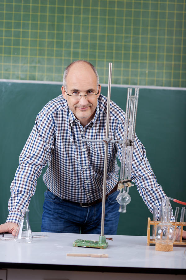 Professeur sûr Leaning On Desk dans la classe de la Science photographie stock libre de droits