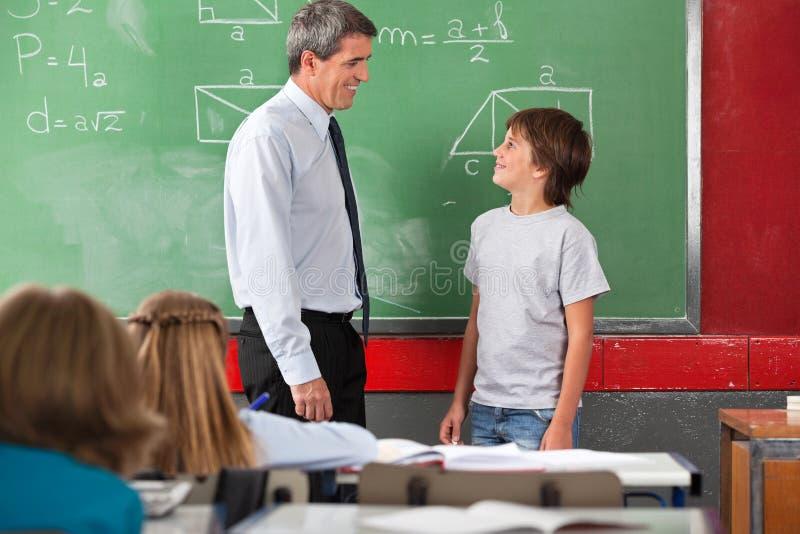 Professeur And Schoolboy Looking à l'un l'autre dedans photos stock