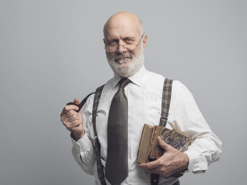 Professeur scolaire posant et fumant un tuyau image stock