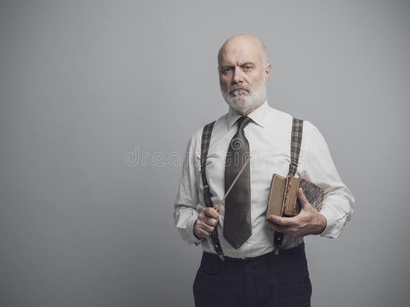 Professeur scolaire sûr posant avec de vieux livres images stock