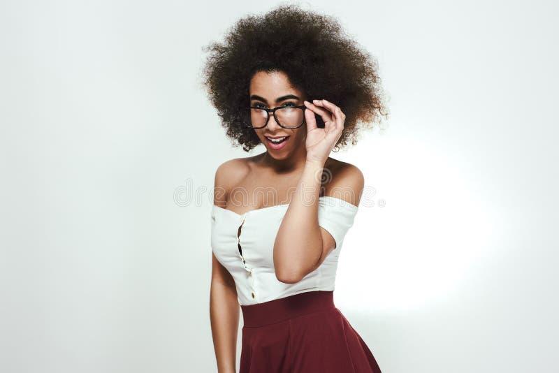 Professeur sexy Portrait de studio de la jeune femme afro-américaine flirty ajustant son eyewear et regardant le moment de caméra photos libres de droits