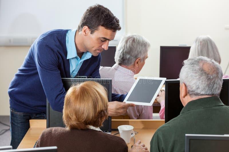 Professeur Showing Digital Tablet aux étudiants en dernière année en Cl d'ordinateur photographie stock libre de droits