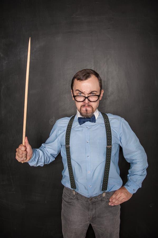 Professeur strict drôle dans des lunettes avec l'indicateur images stock