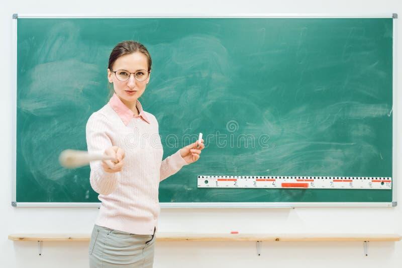 Professeur strict se dirigeant avec l'indicateur devant le tableau noir images libres de droits