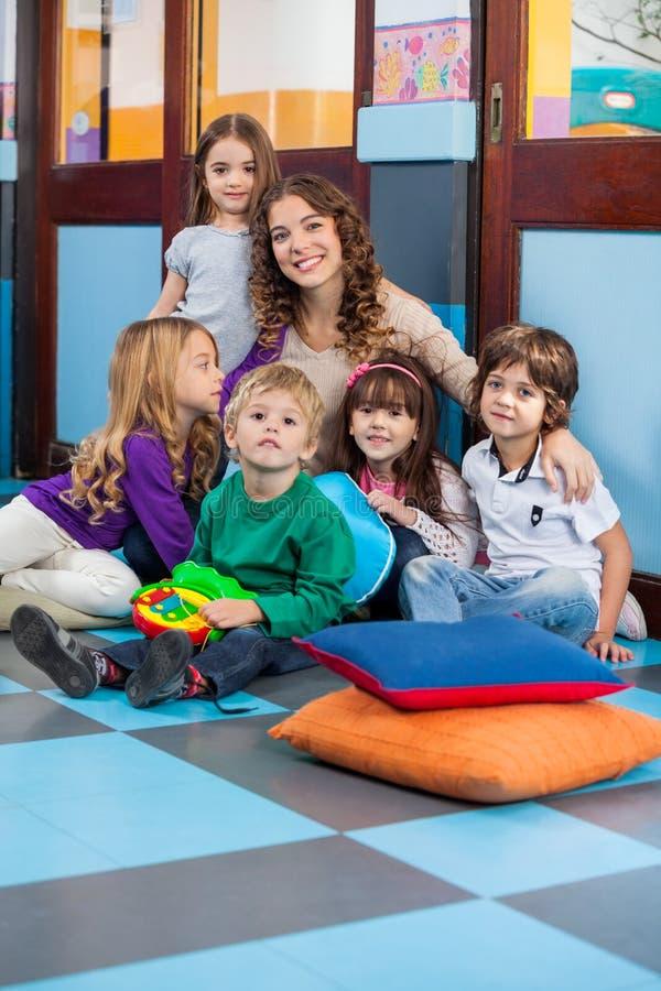 Professeur And Students Sitting sur le plancher dans la salle de classe photo libre de droits