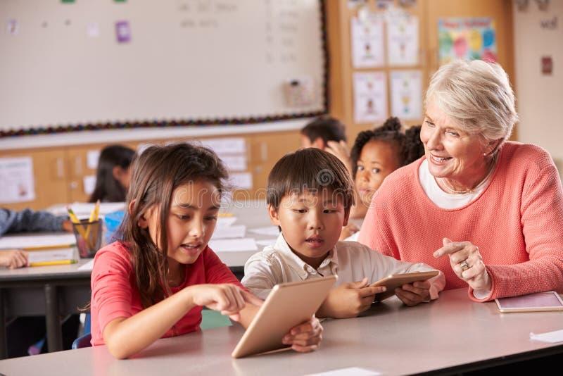 Professeur supérieur aidant des élèves d'école primaire à l'aide du comprimé photos libres de droits