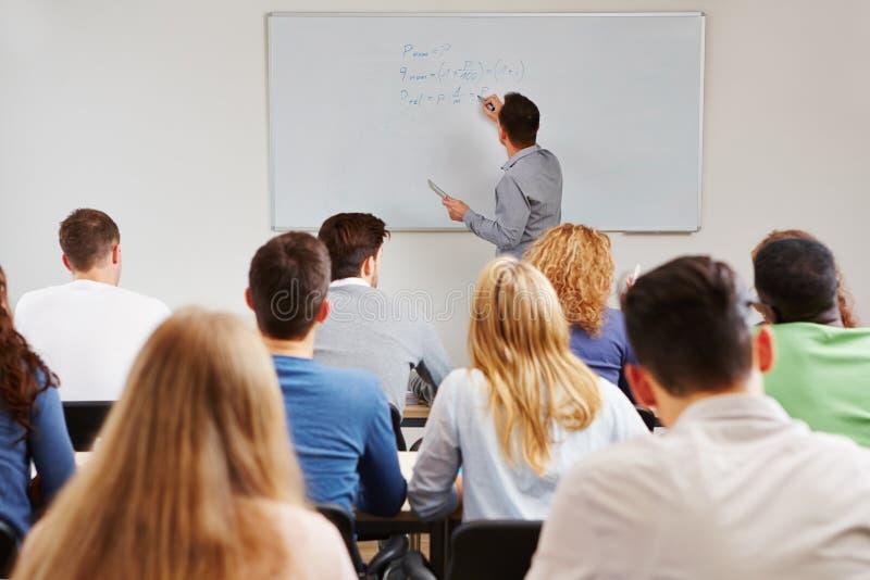 Professeur sur le tableau blanc dans la classe images stock