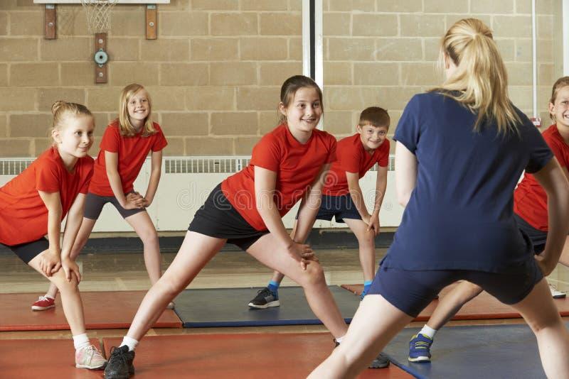Professeur Taking Exercise Class dans le gymnase d'école images stock