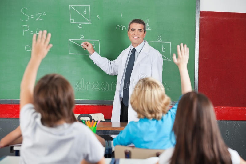 Professeur Teaching While Students soulevant des mains photo stock
