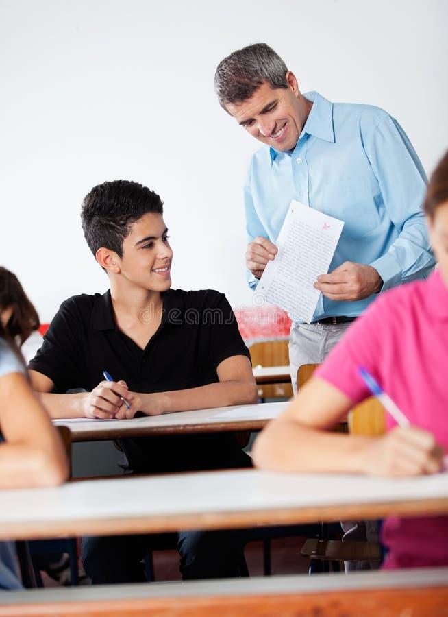 Professeur And Teenage Schoolboy regardant le papier images libres de droits