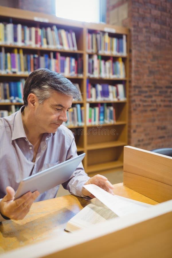 Professeur tenant le comprimé numérique et le livre de lecture photos stock