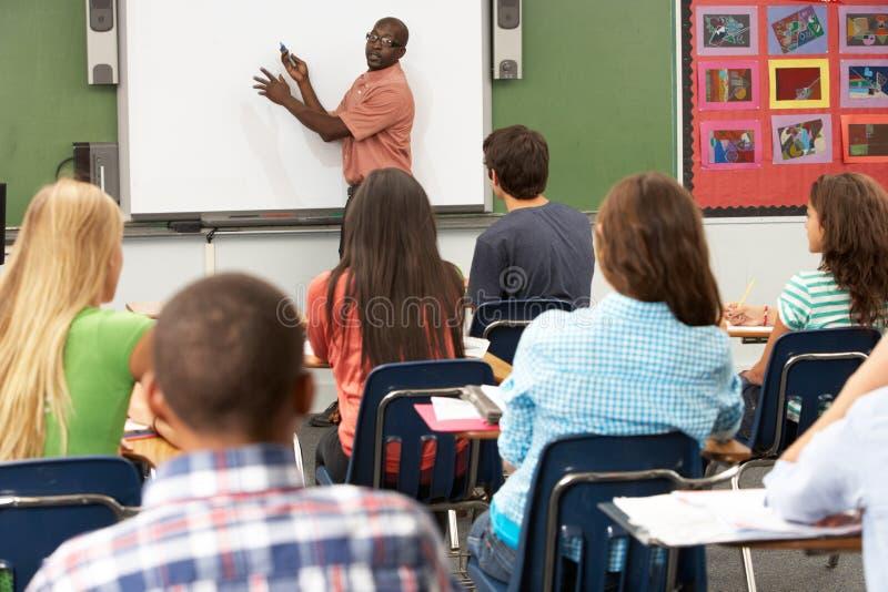 Professeur Using Interactive Whiteboard pendant la leçon photos libres de droits