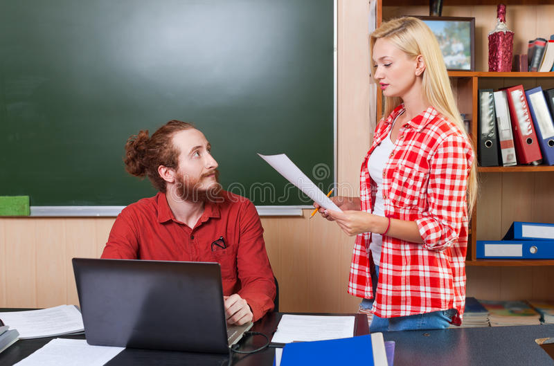 Professeur Using Laptop Computer regardant le jeune étudiant Girl Hold Paper couvre le rapport de document, professeur d'universi photo stock