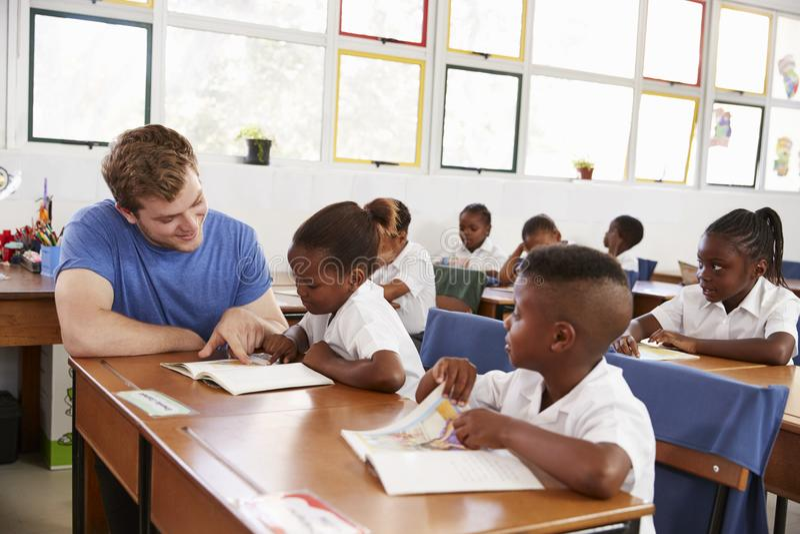 Professeur volontaire aidant la jeune fille à son bureau dans la classe image libre de droits