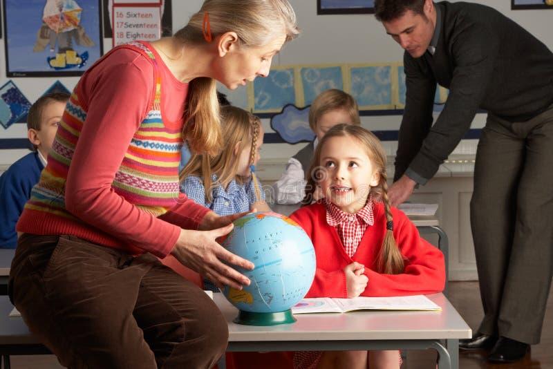 Professeurs donnant la leçon de géographie aux enfants image stock