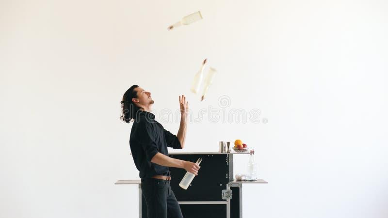 Professinal侍酒者人玩杂耍的瓶和震动鸡尾酒在白色背景的流动酒吧桌上 图库摄影