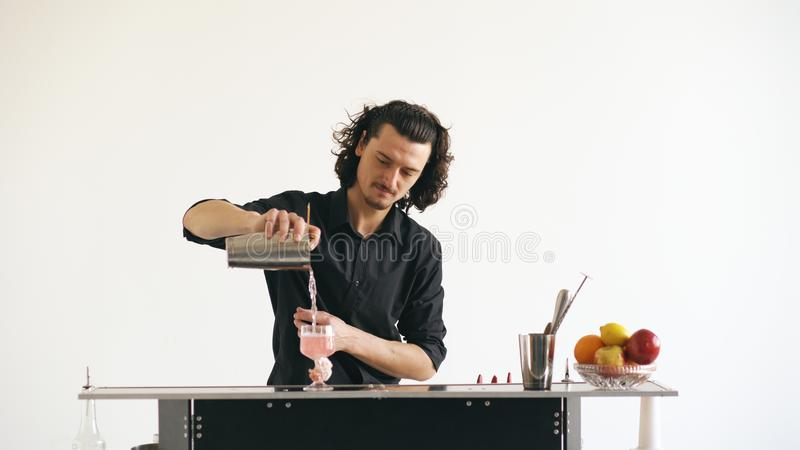 Professinal震动鸡尾酒的侍酒者人在白色背景的流动酒吧桌上 免版税库存图片
