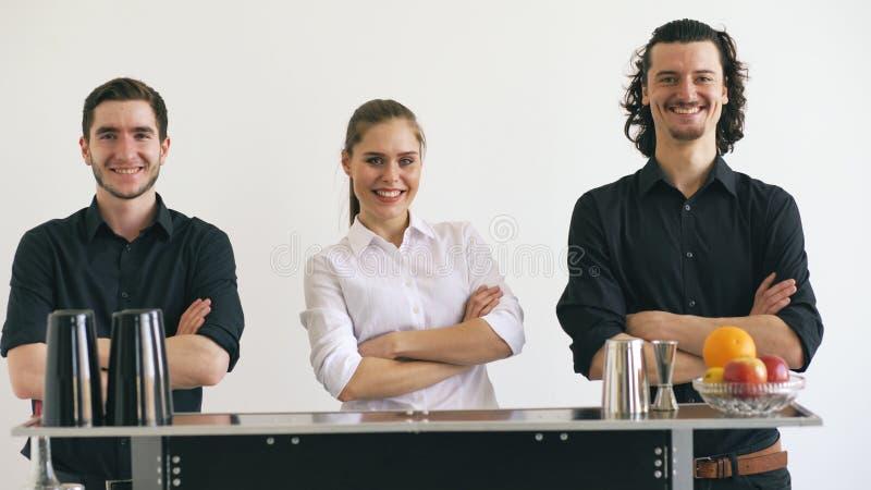 Professinal barmanu mężczyzna i kobieta ono uśmiecha się przy wisząca ozdoba baru stołem na białym tła studiu obrazy stock