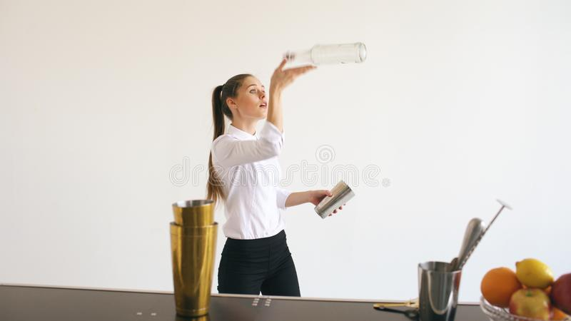 Professinal bartender girl juggling bottles and shaking cocktail at mobile bar table on white background stock photos