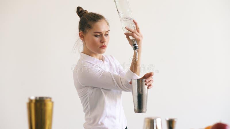 Professinal bartenderflicka som jonglerar flaskor och skakar coctailen på den mobila stångtabellen på vit bakgrund royaltyfria bilder