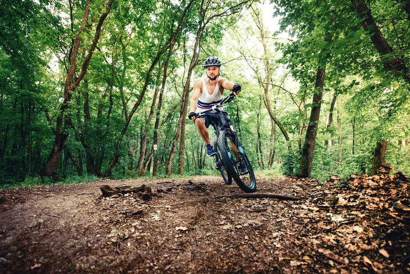 Professioanl biker, extreme sports, cyclist on bike on mountain trail stock images