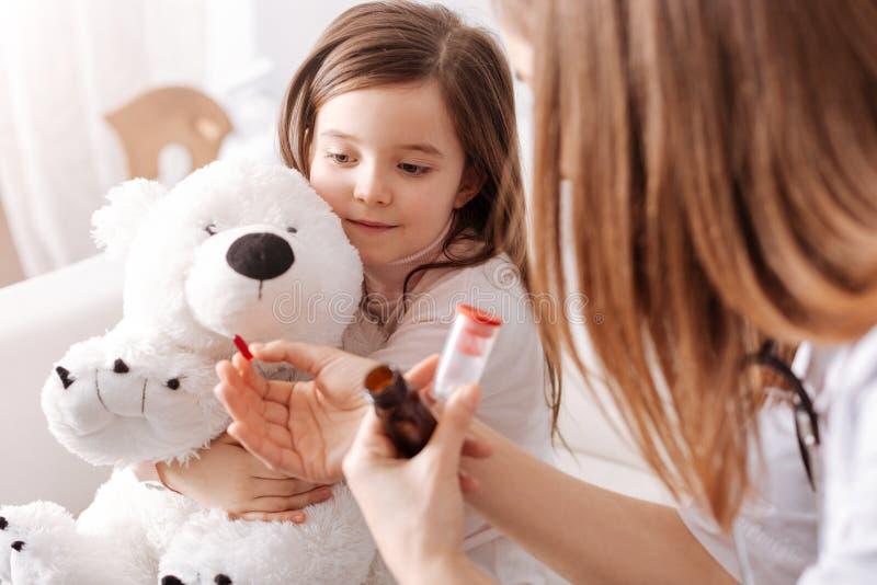 Professioanl Doktor, der einem kleinen Mädchen Pillen gibt lizenzfreie stockbilder