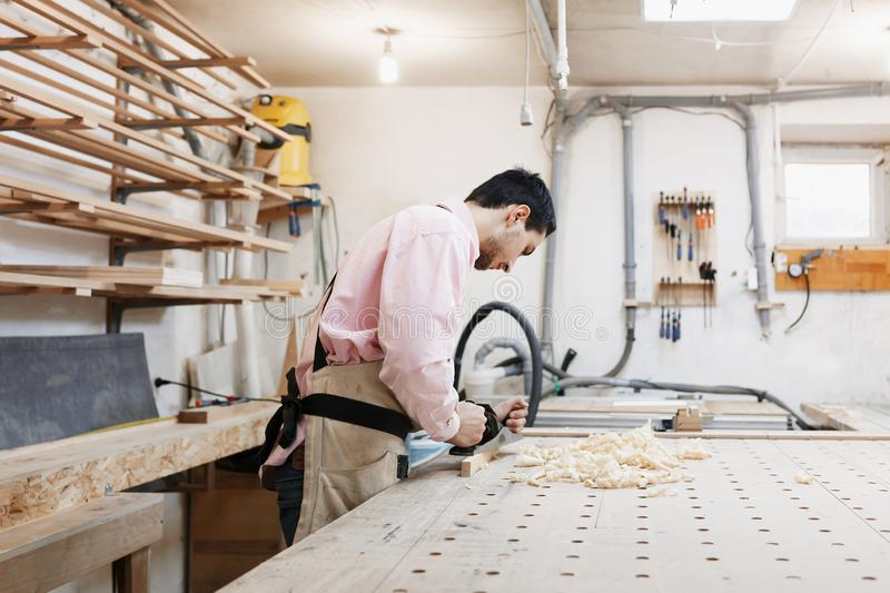 Carpenter working with plane and wood plank at workshop royalty free stock photo