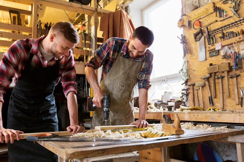 Carpenters working with wooden board at workshop stock photography