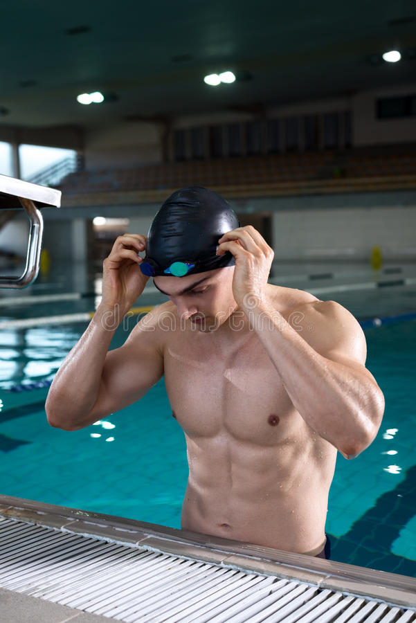Professiona swimmer setting up his goggles for the training royalty free stock photos