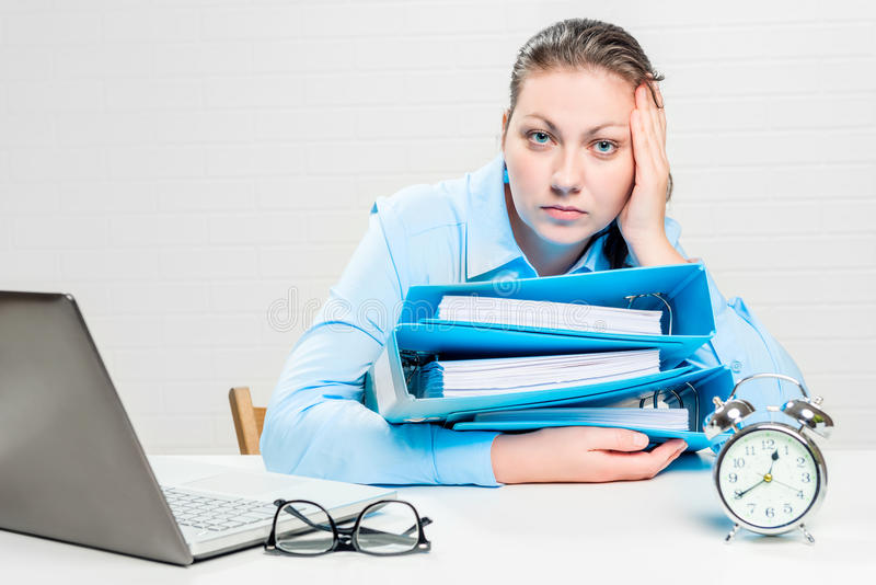 Professional accountant with a bunch of documents working overtime at night stock image