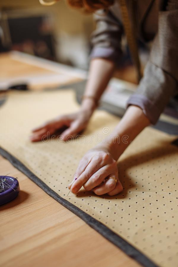 Professional adult female tailor marking cloth pattern with chalk at sewing workshop and looking at camera stock images