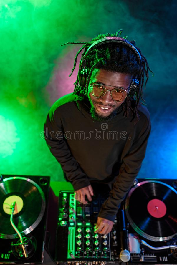 professional african american club DJ in headphones with sound mixer stock images
