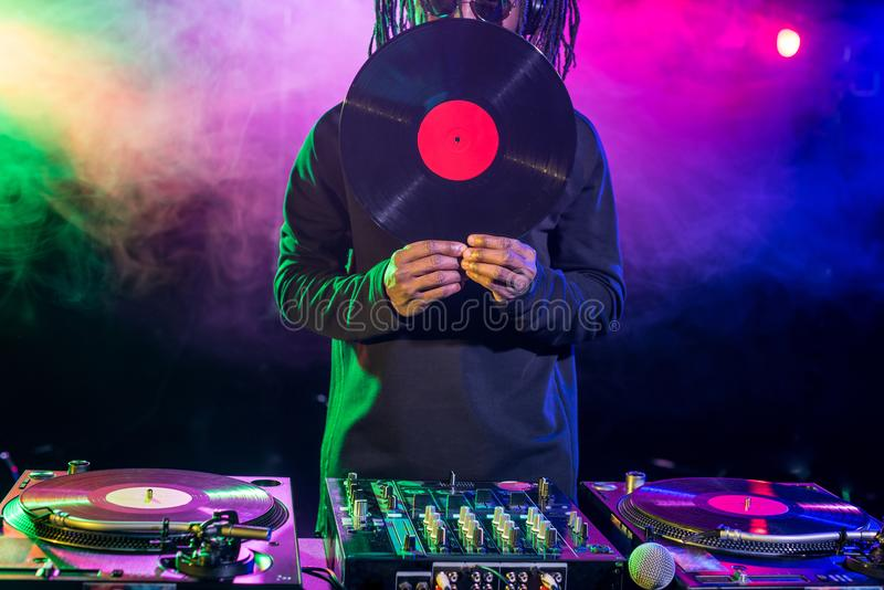 professional african american club DJ with vinyl and sound mixer stock photos
