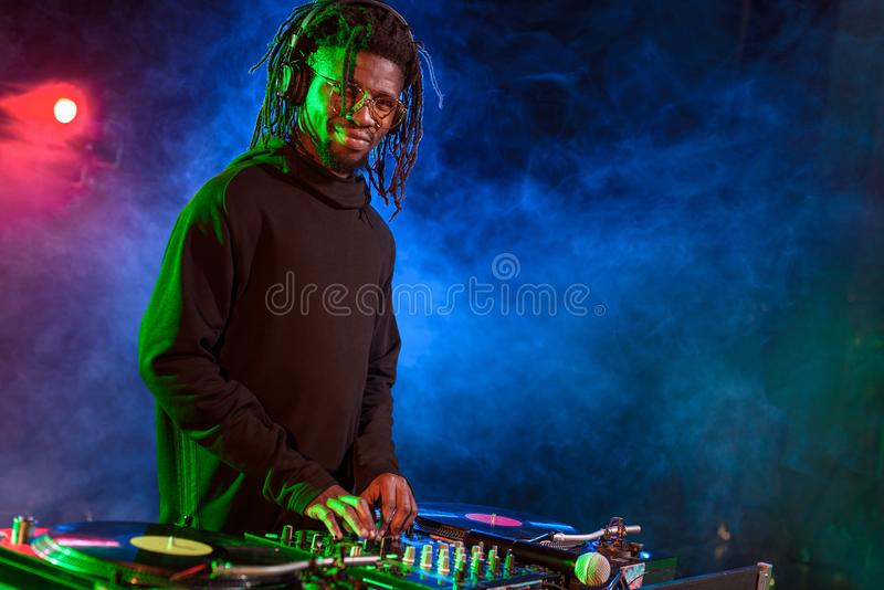 professional african american DJ in headphones with sound mixer stock photography