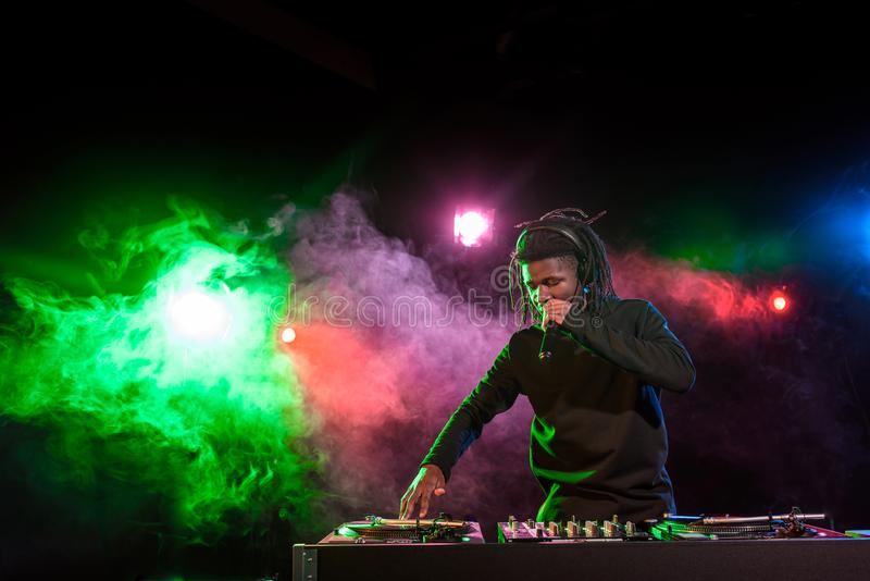 professional african american DJ in headphones with sound mixer royalty free stock photo