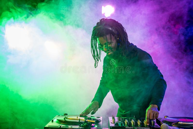 professional african american DJ in headphones with sound mixer royalty free stock photos