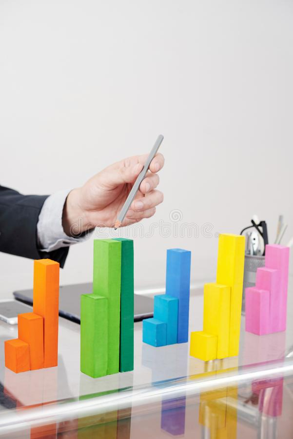 Professional analyst pointing at wooden blocks chart stock photos