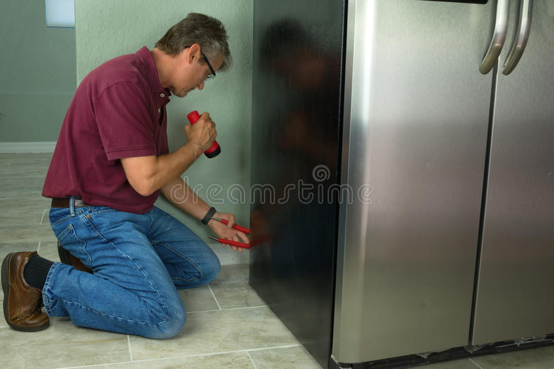A professional appliance repair service technician man repairing. A stainless steel kitchen refrigerator with special tools and flashlight stock images