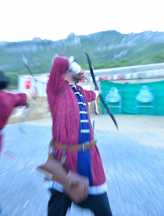 Archery trainings, shots and traditional local outfits. Professional archer`s working moment ;sport concept royalty free stock photography