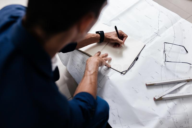 Professional architect makes notes in a notebook on a table with a drawing and ruler royalty free stock photos