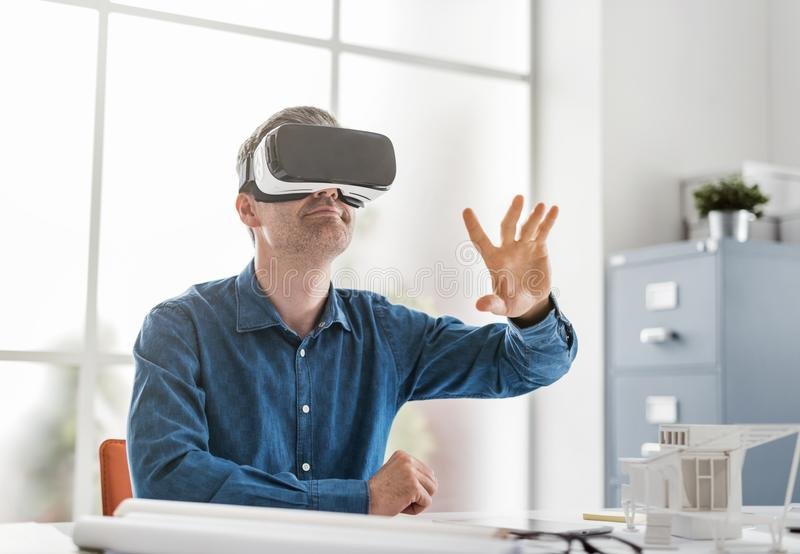 Professional architect working with virtual reality headset and interacting with a virtual environment, innovation and technology stock image