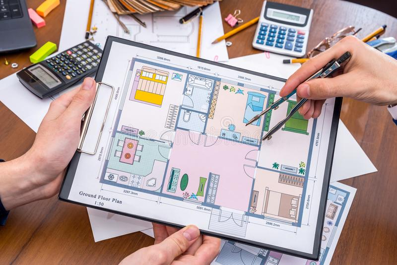 Professional architects discussing the house project. With work tools royalty free stock image