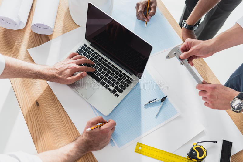Professional architects in formal wear working with laptop at modern office. Businessmen group royalty free stock images