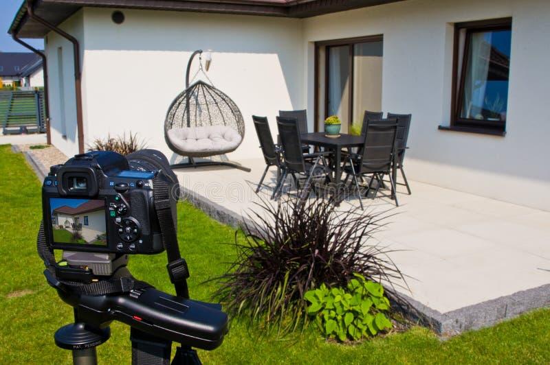 Shooting house exterior, photographer camera, tripod and ballhead royalty free stock image