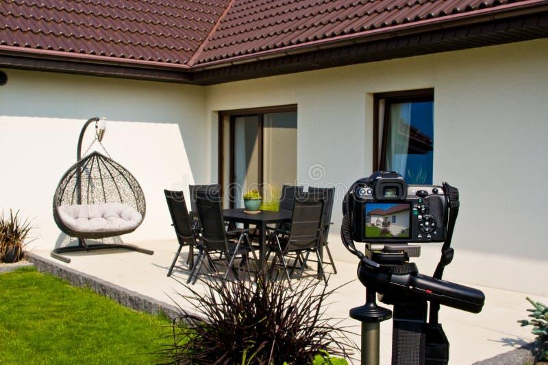 Shooting house exterior, photographer camera, tripod and ballhead royalty free stock photos