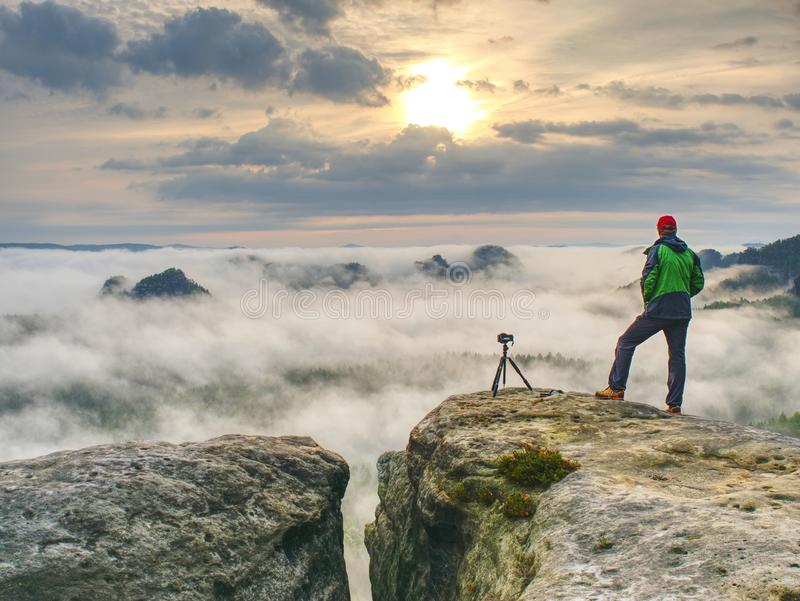 Professional artist on cliff. Nature photographer takes photos stock photography