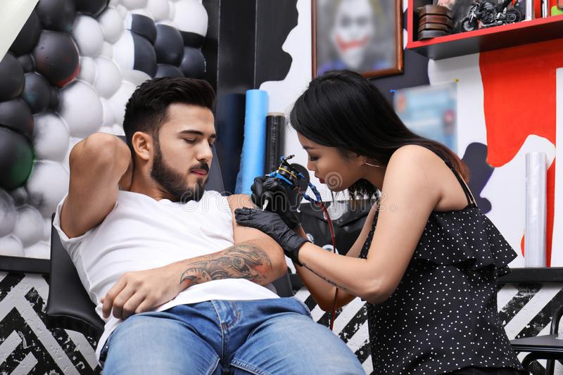 Professional artist making tattoo with machine. In salon royalty free stock images