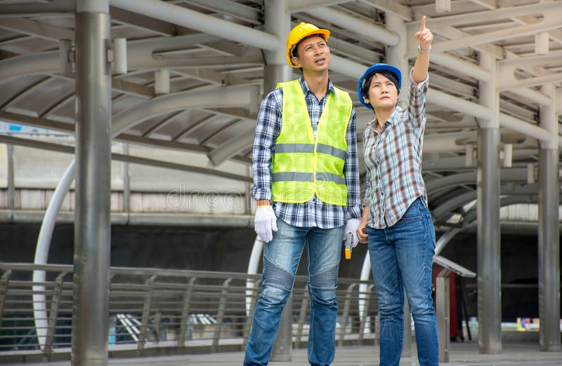 Professional Asian engineering team wearing safety helmet talking about construction project and pointing finger up at stock photos
