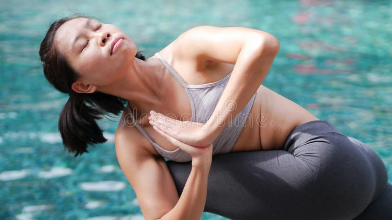 Professional asian woman practice yoga sequence Revolved Side Angle Pose royalty free stock images