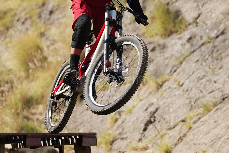 Professional athlete high jumping downhill on the mountain bike stock photography
